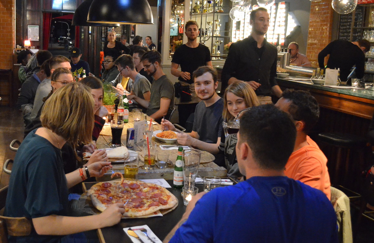 Students with a big pizza in Germany